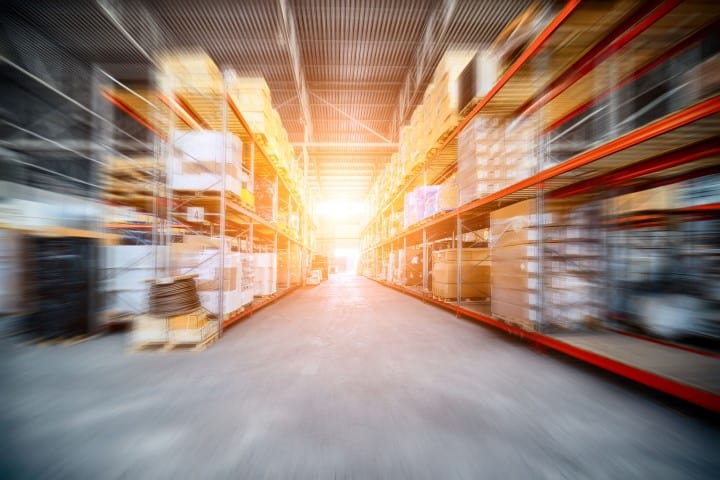 Warehouse industrial and logistics companies. The boxes on high shelves stocked. Motion blur effect. Bright sunlight.