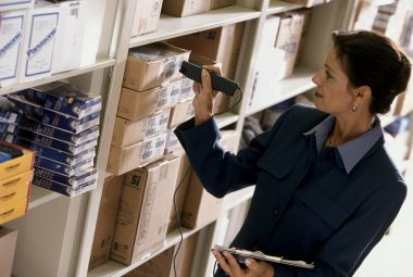 Mid adult woman checking the bar code on products in a warehouse